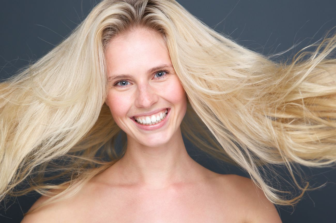 Close up portrait of a joyful young blond woman with beautiful hair